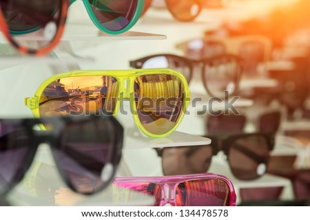 Many colorful sunglasses on display - stock photo