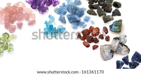 Many colorful uncut gems on the white. Beautiful gemstones background image. - stock photo