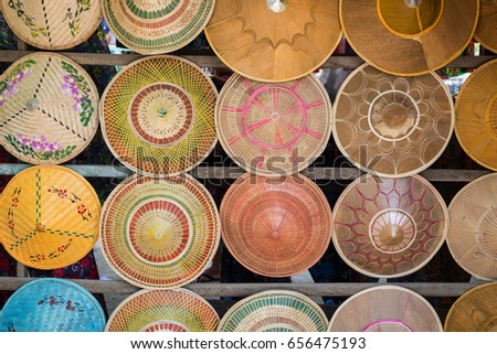 Many colorful woven Asian conical hats (also known as Asian rice hats or farmer's hats) for sale in Myanmar (Burma).