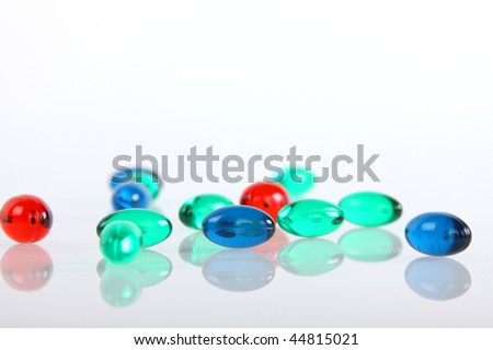Many colors pills on white background