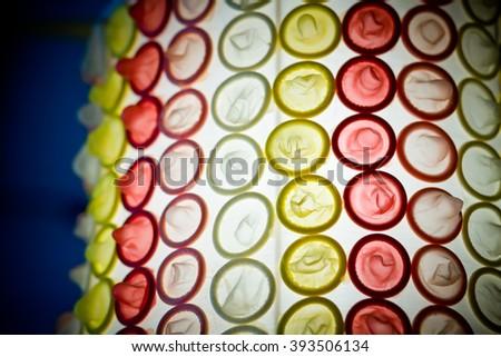 Many colourful condoms - stock photo