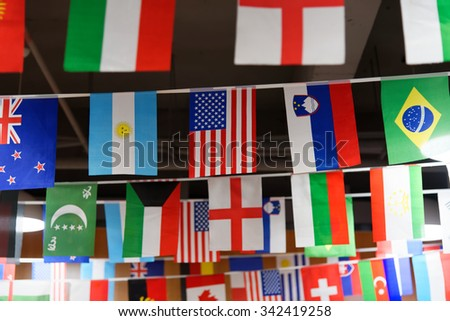 Many countries flags hanging from a ceiling on ropes around the American flag - stock photo