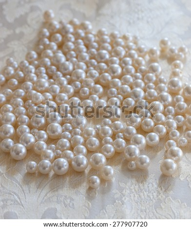 Many cream-colored pearls lie close together on a bright, festive tablecloth  - stock photo