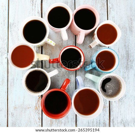 Many cups of coffee on wooden background - stock photo