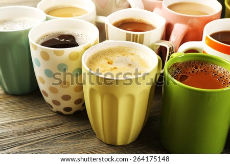 Many cups of coffee on wooden table, closeup - stock photo