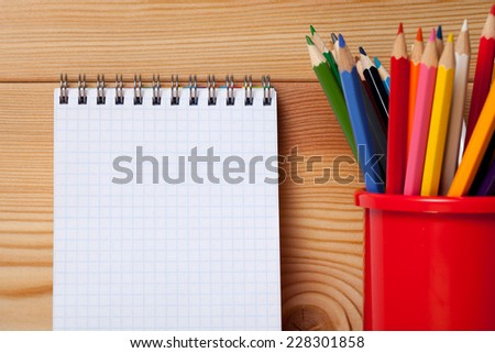 Many different colored pencils on wooden table and empty notebook blank. - stock photo