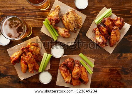 many different flavored buffalo chicken wings with beer party sampler sharing platter shot from top down view - stock photo
