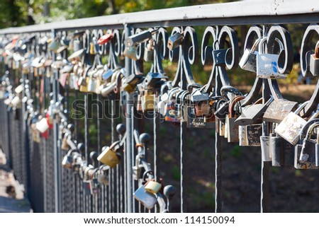 Many different locks hung on a bridge. These locks newlyweds hang a sign of eternal love. - stock photo