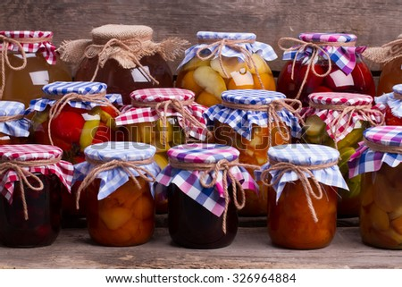 Many different preservation on the old wooden boards. Canned fruits and vegetables in the cellar. - stock photo