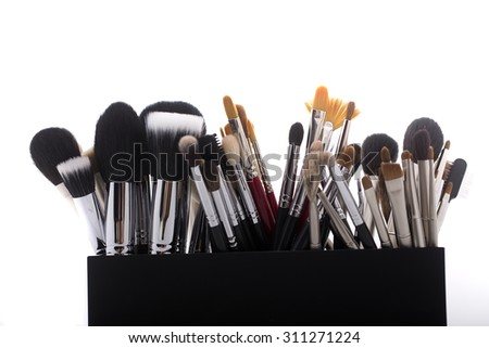 Many different professional natural soft make-up brushes for eyeshadow powder and facial foundation for visagistes black and brown colors in plastic box on white background, horizontal picture - stock photo