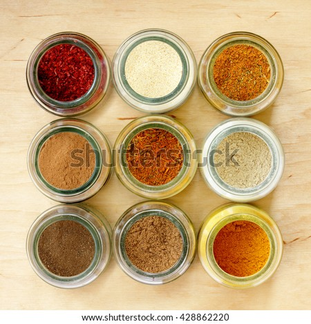 many different spices in glass jars, and a special seasoning for pilaf in the middle of a top view / aromatic seasoning for cooking in the kitchen - stock photo