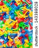 Many different toy puzzle mosaic pieces of different colors laying in a pile, red, yellow, green, blue - stock photo