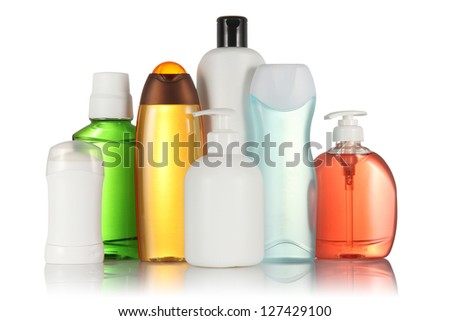 Many different white, green, red, blue and orange tubes and bottles for hygiene, health and beauty on a white background with reflection isolated. - stock photo