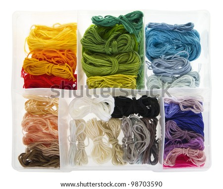 Many differently coloured embroidery threads, neatly boxed. Isolated on white background. - stock photo