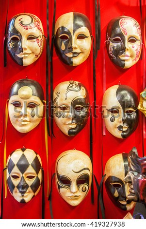 Many distinctive Venetian carnival masks of various colors, red background - stock photo