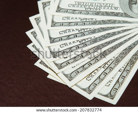Many dollar's banknotes on brown background