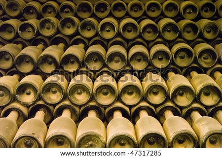 Many dusted wine bottles in an old cellar