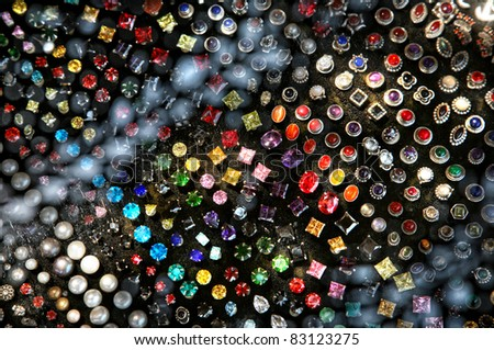 Many earrings in different color with gem in Goa, Anjuna flea market, India - stock photo