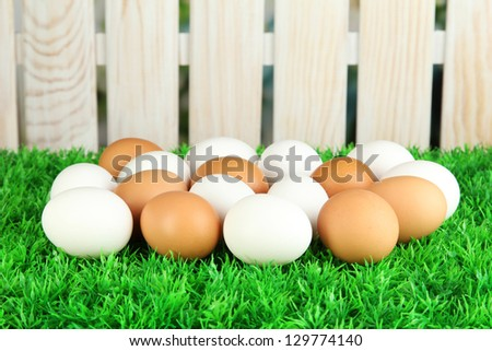 Many eggs on grass on bright background - stock photo