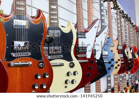 Many electric guitars hanging on wall in the shop - stock photo