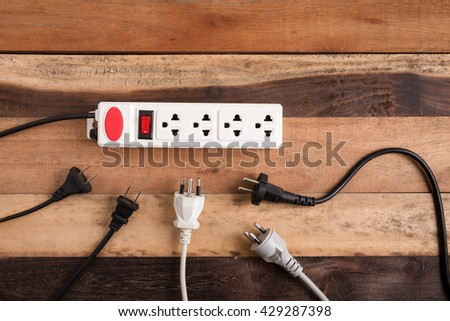 Many electrical plugs connected to a power strip or extension block on wooden table - stock photo
