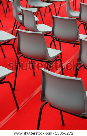 Many empty chairs arranged on the red carpet