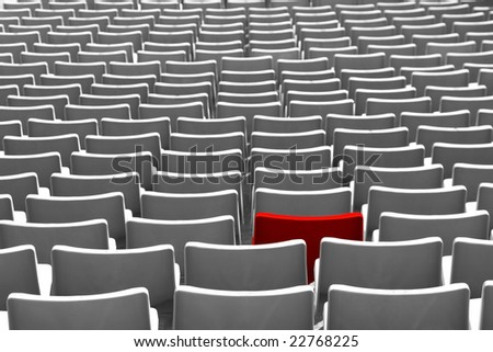 Many empty uniform seats with one red seat - stock photo