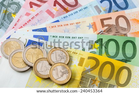 Many euro banknotes and coins, closeup shot - stock photo