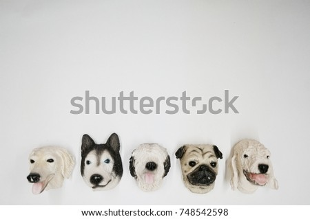 Many faces of various dog breeds on the white background