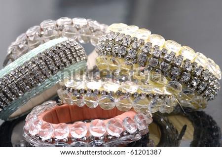 Many fashion colorful brilliant bangles on gray - stock photo