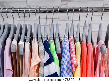 many female colorful shirt hanging on hangers at store