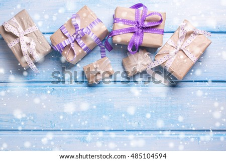 Many  festive gift boxes with presents on blue wooden background. Christmas background. Selective focus. Place for text. Drawn snow effect.