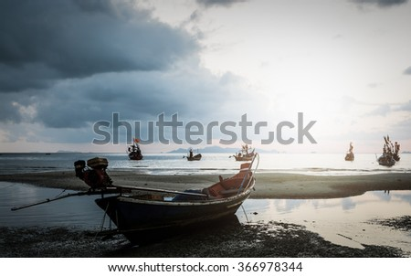 Many fishing boat in the sea when low tide under the sunlight