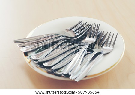 many fork in the ceramic plate on wooden background.