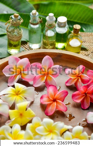 many frangipani in bowl with oil, green leaf on mat