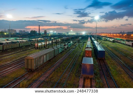 Many freight cars standing on railroad at late dusk time - stock photo