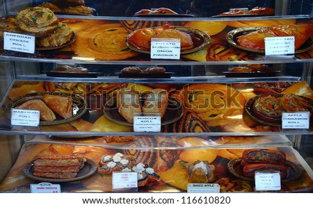 Many fresh baked pastries in a case at a bakery shop