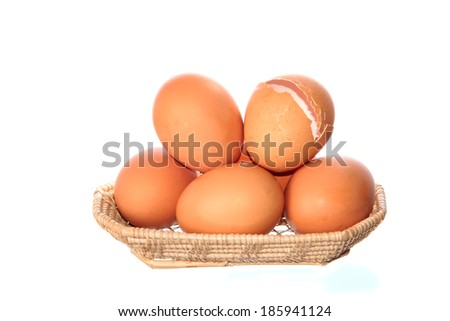 many fresh chicken eggs in wicker basket isolated on white background