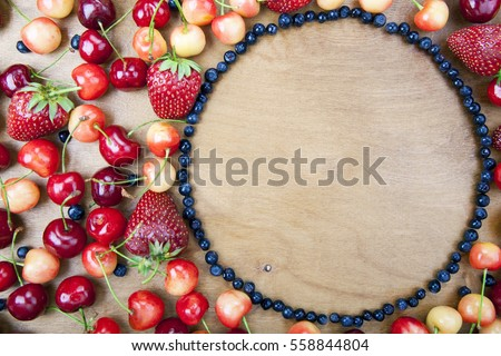 Many fresh fruit lying around the circle of blueberries on a wooden boards background
