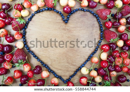 Many fresh fruit lying around the heart of blueberries on a wooden boards background