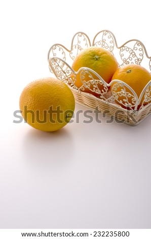 many fresh oranges in the basket on white background - stock photo
