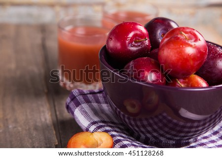 many fresh ripe wet plum with juice in glass and basil