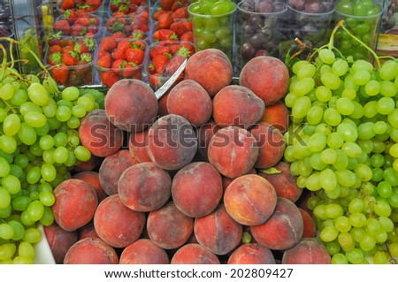 Many fruits including peach uve strawberry on a supermarket shelf