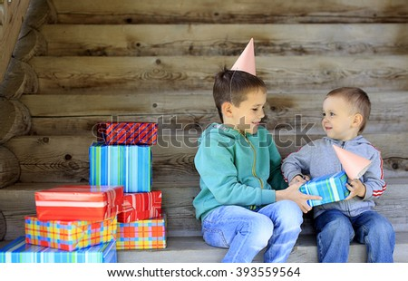 many gifts on the child's birthday. children's birthday party. brothers going to unwrap gifts - stock photo