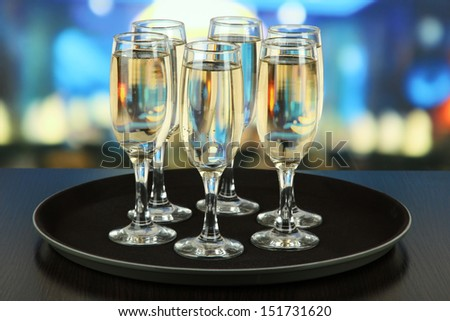Many glasses of champagne on the tray on table, on bright background - stock photo