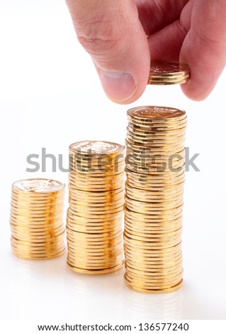 Many gold coins stacked by hand isolated on a white background.