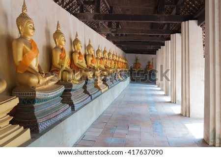 Many golden buddha statue along walkway in thai temple