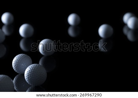 Many golf balls isolated on black background with empty copy space for text. - stock photo
