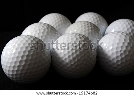 many golf balls on the black background