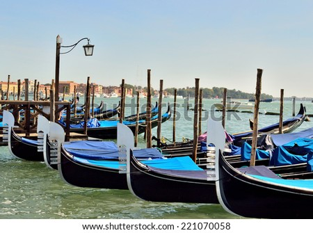 many gondola stand on the dock in Venice